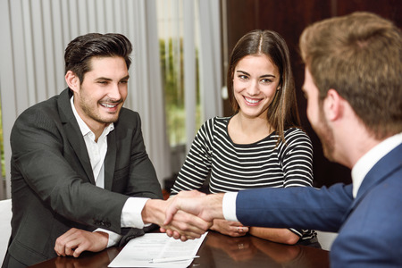 Foto de Smiling young couple shaking hands with an insurance agent or investment adviser - Imagen libre de derechos