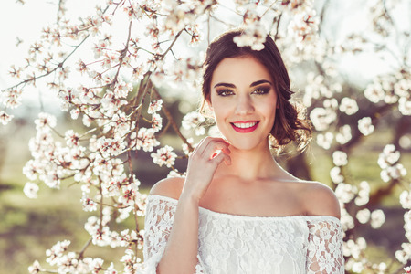 Photo pour Portrait of young woman smiling in the flowered garden in the spring time. Almond flowers blossoms. Girl dressed in white like a bride. - image libre de droit