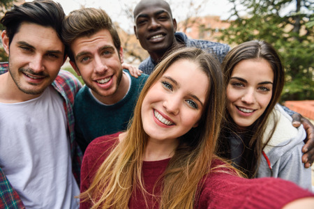 Foto de Multiracial group of friends taking selfie in a urban park with a blonde young girl in foreground - Imagen libre de derechos