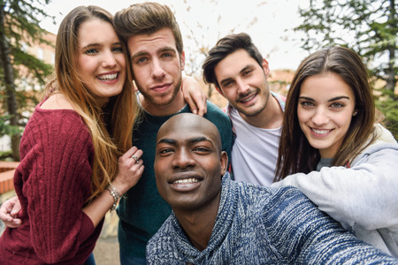 Photo pour Multiracial group of friends taking selfie in a urban park with a black man in foreground - image libre de droit