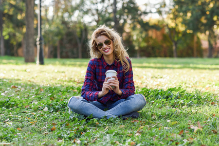 Photo pour Young happy Woman in checkered shirt and blue jeans with toothy Smile and sunglasses. Blonde girl drinking coffee in park sitting on grass wearing casual clothes smiling - image libre de droit