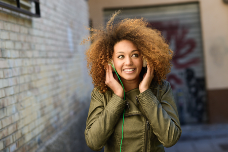 Photo pour Portrait of young attractive black girl in urban background hearing music with headphones - image libre de droit