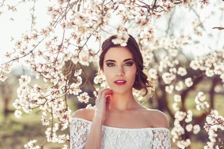 Photo pour Portrait of young woman in the flowered garden in the spring time. Almond flowers blossoms - image libre de droit