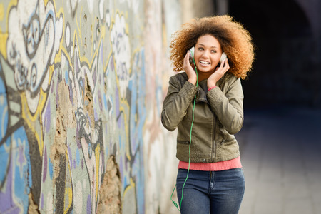 Photo pour Portrait of young attractive black girl in urban background listening to the music with headphones. Woman wearing leather jacket and blue jeans with afro hairstyle - image libre de droit