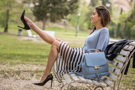 Foto de Portrait of young woman with beautiful legs in urban park wearing casual clothes. Girl wearing striped skirt, sweater and high heels - Imagen libre de derechos