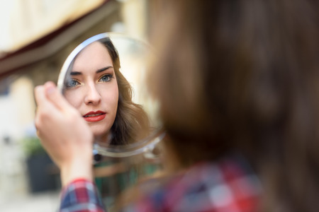 Photo pour Portrait of young woman looking at herself in a little mirror in urban background. - image libre de droit