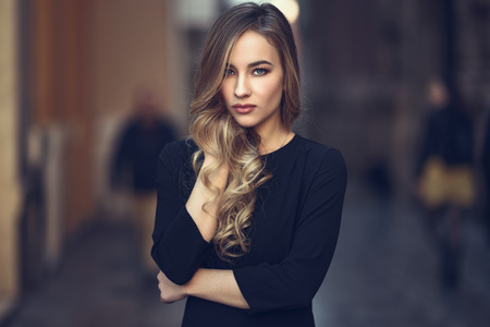Foto de Blonde woman in urban background. Beautiful young girl wearing black elegant dress standing in the street. Pretty russian female with long wavy hair hairstyle and blue eyes. - Imagen libre de derechos