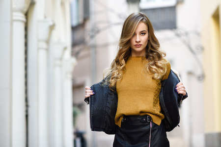 Photo for Blonde woman in urban background. Beautiful young girl wearing black leather jacket and mini skirt standing in the street. Pretty russian female with long wavy hair hairstyle and blue eyes. - Royalty Free Image
