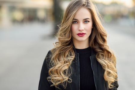 Foto de Close-up portrait of young blonde girl with beautiful blue eyes wearing black jacket outdoors. Pretty russian female with long wavy hair hairstyle. Woman in urban background. - Imagen libre de derechos