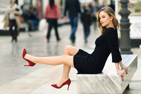 Foto de Funny blonde woman with beautiful legs in urban background. Beautiful young girl wearing black elegant dress and red high heels sitting on a bench in the street. Pretty russian female with long wavy hair hairstyle and blue eyes. - Imagen libre de derechos