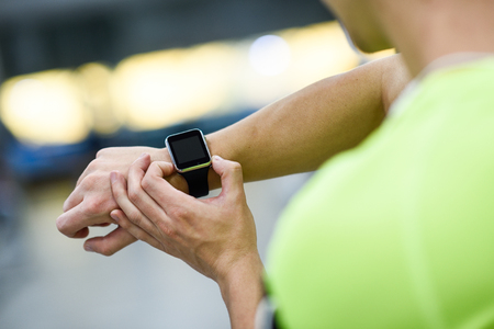 Photo for Young man using smartwatch at the gym. Caucasian male working out. - Royalty Free Image