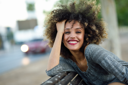 Photo for Young mixed woman with afro hairstyle smiling in urban background. Black girl wearing casual clothes. - Royalty Free Image