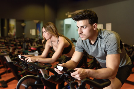 Foto per Attractive woman and man biking in the gym, exercising legs doing cardio workout cycling bikes. Couple in a spinning class wearing sportswear. - Immagine Royalty Free