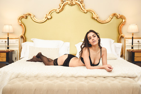 Photo for Sexy young woman in lingerie posing on the bed. Brunette girl with black underwear in her bedroom - Royalty Free Image