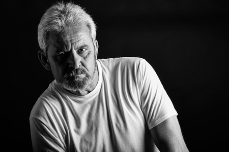 Foto de Portrait of a serious mature man looking at camera. Senior male with white hair and beard wearing casual clothes isolated on black background. Studio shot in black and white. - Imagen libre de derechos