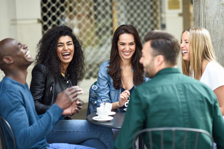 Foto de Multiracial group of five friends having a coffee together. Three women and two men at cafe, talking, laughing and enjoying their time. Lifestyle and friendship concepts with real people models - Imagen libre de derechos