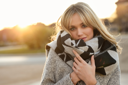 Foto de Attractive blonde woman in urban background with sun backlight. Young girl wearing winter coat and scarf standing in the street. Pretty female with straight hair hairstyle and blue eyes. - Imagen libre de derechos