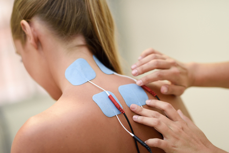 Foto de Electro stimulation in physical therapy to a young woman. Medical check at the shoulder in a physiotherapy center. - Imagen libre de derechos