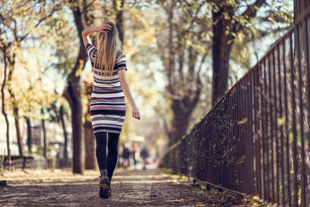 Foto de Young blonde woman walking in the street. Beautiful girl in urban background wearing striped dress and black tights. Female with straight hair. Back view - Imagen libre de derechos
