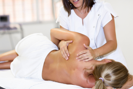 Photo pour Professional female physiotherapist giving shoulder massage to blonde woman in hospital. Medical check at the shoulder in a physiotherapy center. - image libre de droit