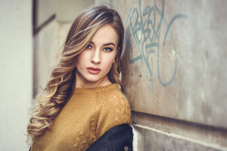 Foto de Blonde woman in urban background. Beautiful young girl wearing black leather jacket and mini skirt standing in the street. Pretty russian female with long wavy hair hairstyle and blue eyes. - Imagen libre de derechos