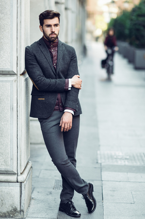 Photo for Young bearded man, model of fashion, standing in urban background wearing british elegant suit. Guy with beard and modern hairstyle in the street. - Royalty Free Image