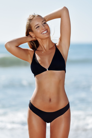 Foto de Young blonde woman with beautiful body in swimwear smiling on a tropical beach. Caucasian female with straight long hairstyle wearing black bikini. - Imagen libre de derechos
