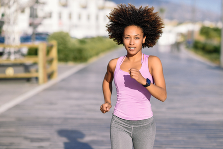 Photo for Black woman, afro hairstyle, running outdoors in urban road. Young female exercising in sport clothes. - Royalty Free Image