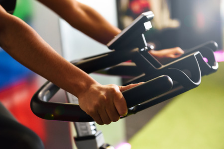 Photo pour Close-up of woman's hands training at a gym doing spinning or cyclo indoor. Sports and fitness concept. - image libre de droit
