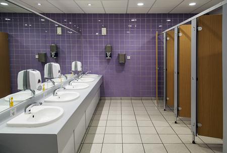 Foto de Public bathroom. Ladies restroom with cubicles and sinks and a purple tiled wall. - Imagen libre de derechos
