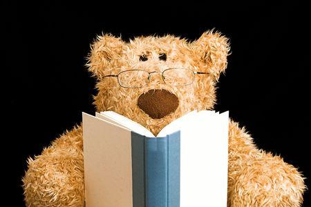 Photo pour teddy bear with glasses reading a book - image libre de droit