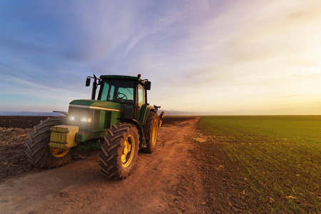 Photo pour Green tractor on field at sunset after plowing - image libre de droit
