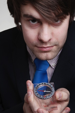 businessman holding up to his face a compass so he can see where he is going