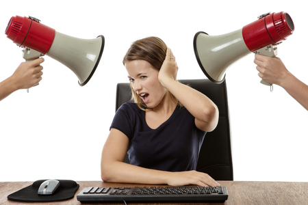 business woman sitting at her desk being shouted at with a bullhorn