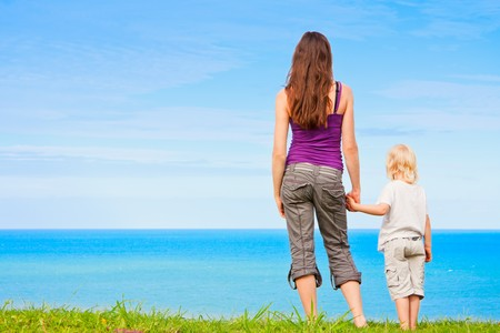 Photo for A young mother and child holding hands and looking at beautiful ocean view - Royalty Free Image