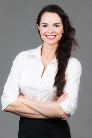 Portrait of a happy young business woman with arms folded, over grey background