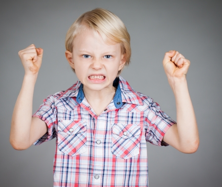 Foto de A frustrated and angry looking young boy with fists clenched and pulling a face. Isolated on white. - Imagen libre de derechos