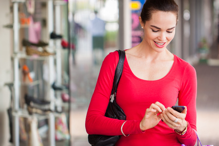Foto de happy beautiful woman texting on a mobile or smart phone whilst out shopping. - Imagen libre de derechos