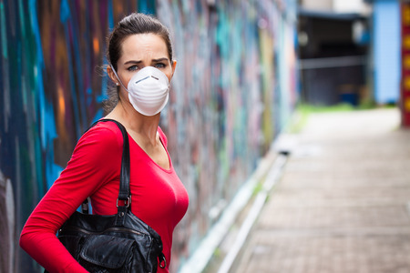 Photo for A woman on a street wearing a face mask looking upset - Royalty Free Image