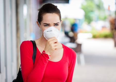 Photo for A woman wearing a face mask in the city coughing  - Royalty Free Image
