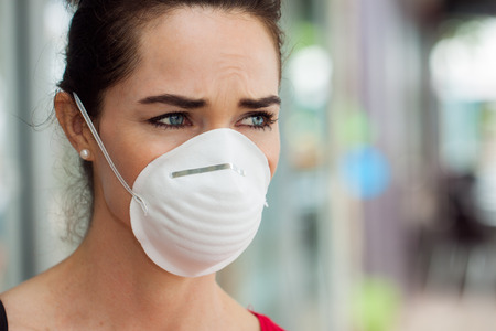 Photo for Close-up of a woman in the city wearing a face mask to protect herself from infection or air pollution  - Royalty Free Image