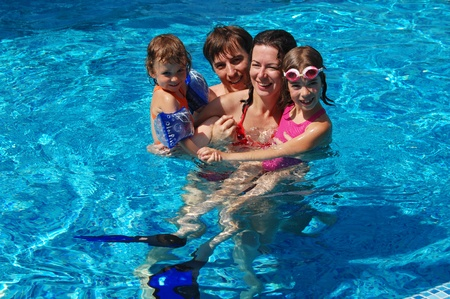 Happy family with two kids having fun in swimming pool