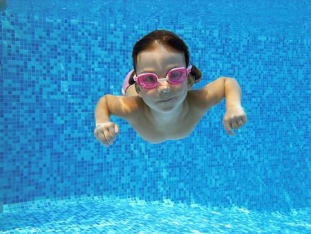 Kid swimming underwater in the pool
