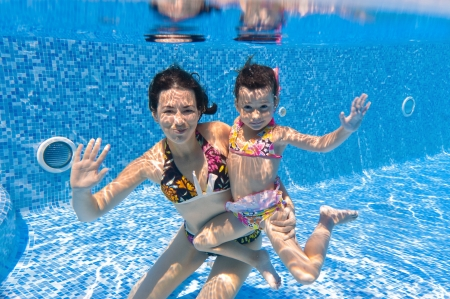 Underwater smiling family in swimming pool