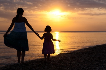 Photo for Mother and kid on sunset beach - Royalty Free Image