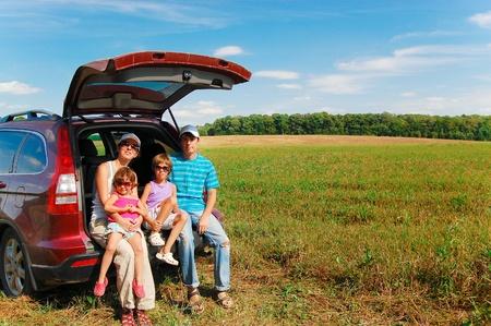 Photo pour Family of four near their car on vacation - image libre de droit