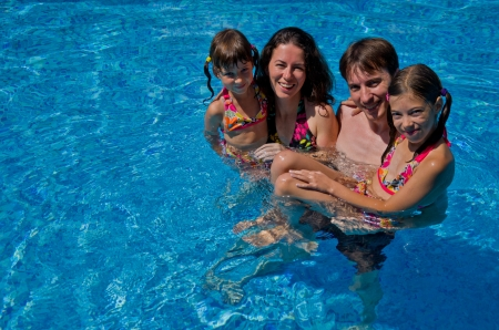 Happy family with two kids in swimming pool  Smiling parents and children on summer vacation swim and having fun  Family sport, active healthy holiday