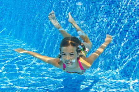 Happy smiling underwater child in swimming pool, beautiful healthy girl swims and having fun in water  Kids sport on family summer vacation  Active holiday