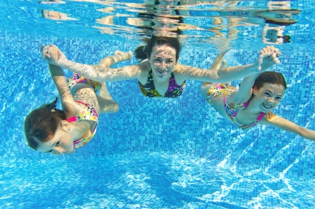 Happy smiling family underwater in swimming pool. Mother and children swim and having fun. Kids sport on family summer vacation. Active healthy holiday