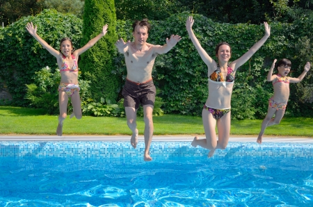 Happy family with kids jumping to swimming pool, smiling parents and children having fun on summer vacation